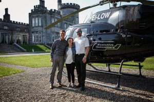 Couple standing beside a helicopter with the pilot, at Dromoland castle before a marriage proposal