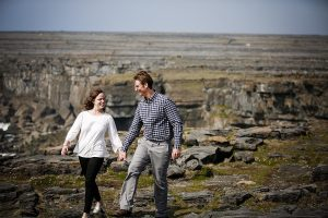 Couple walking hand in hand along a cliff edge